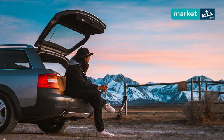Мужчина сидит на багажнике автомобиля